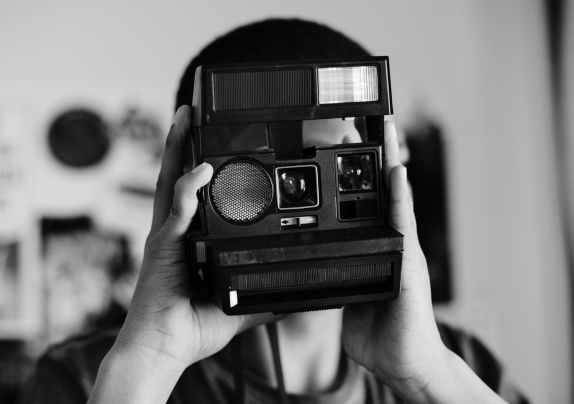 grayscale photo of person holding a camera